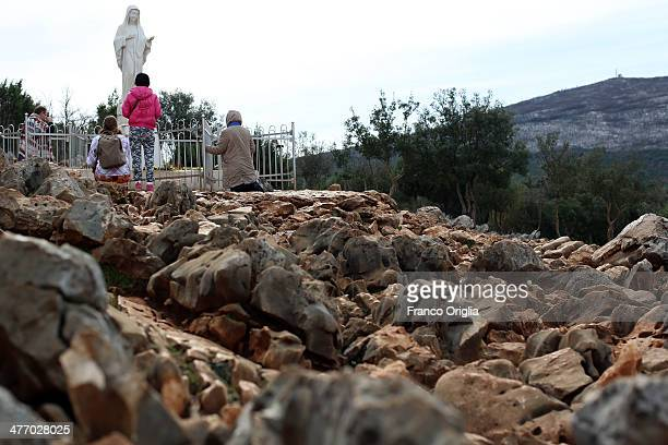 Pilgrims visit the statue of the Virgin Mary at one of the sites of the Marian apparitions on March 6 2014 in Medjugorje Bosnia and Herzegovina Since...