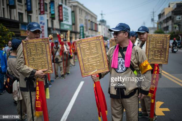 Pilgrims wait for the arrival of the sedan chair carrying a statue of the goddess Mazu as it is carried along on day two of the nine day Mazu...