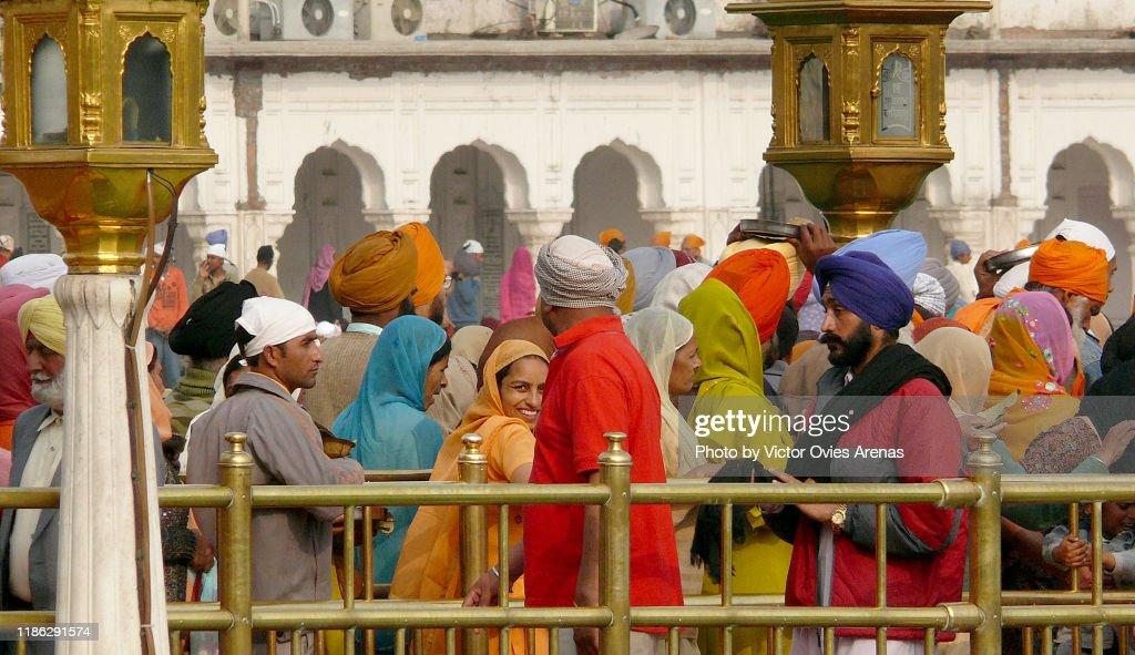 Pilgrims waiting to enter the Harmandir Sahib (The Golden Temple) and the clock tower in Amritsar, Punjab, India : Foto de stock