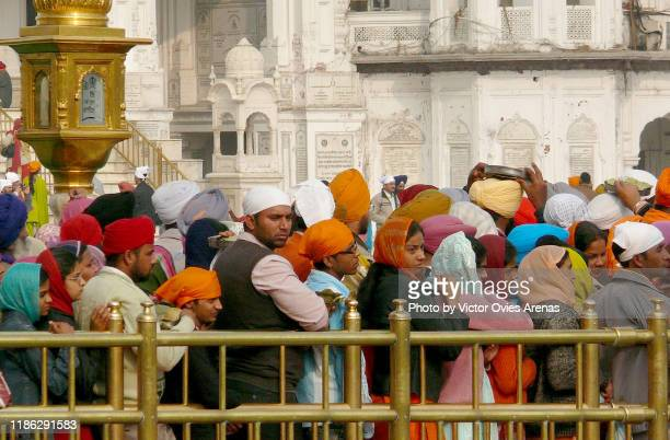 pilgrims waiting to enter the harmandir sahib (the golden temple) and the clock tower in amritsar, punjab, india - victor ovies fotografías e imágenes de stock