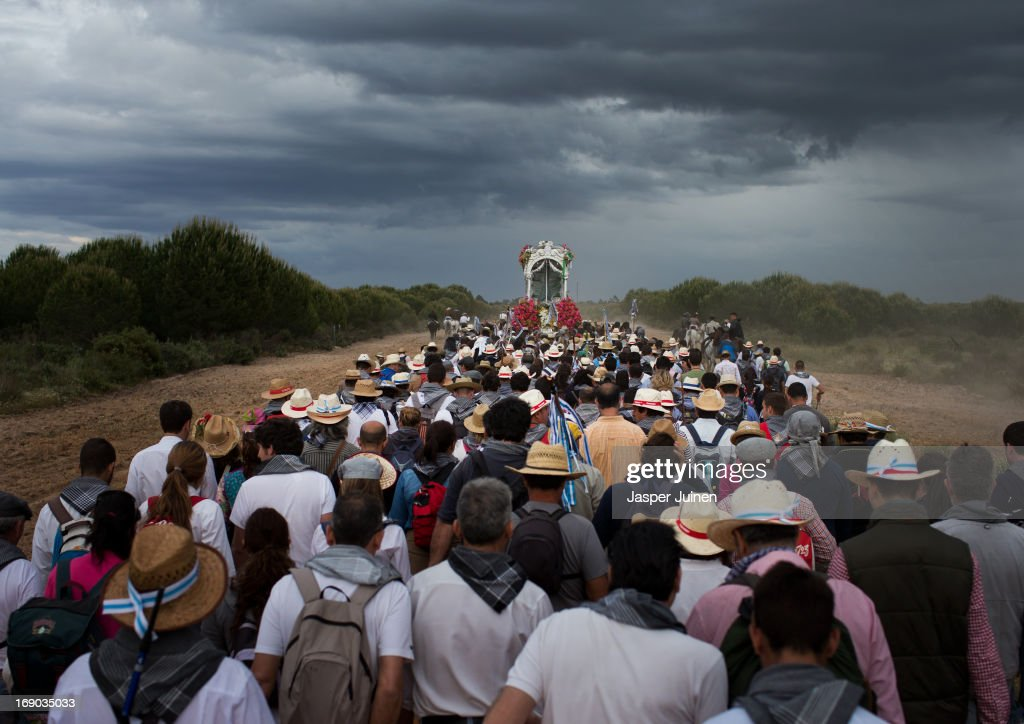 Pilgrims walk behind the carriage carrying the Simpecado of the Hermandad del Rocio de Huelva during their journey to La Ermita del Rocio on May 16, 2013 in Huelva, Spain. The Romeria del Rocio procession brings together roughly a million pilgrims each year making their way for as long as seven days from throughout Andalusia by foot, on horsebacks and horse drawn carriages, to the doors of the Hermitage of El Rocio. On Sunday night, after reciting the Holy Rosary at candlelight, and the passing of all the simpecados in front of the chapel, with the one from the brotherhood of Matriz de Almonte as the last one, el salto de la reja begins, the jumping of the fence surrounding the Hermitage after which the Virgin of El Rocio is carried out onto the sandy streets of the small town for the 'Blanca Paloma' procession. Then, the long camino home begins. Dating back from 1653, it was in 1758, when the Virgin of Las Rocinas became known as the Virgin of El Rocio, that the pilgrimage started to take place in the weekend of the Sunday of Pentecost, 50 days after Easter Sunday.