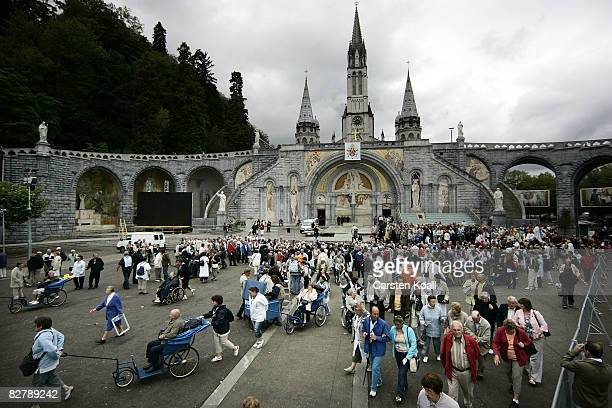 Pilgrims walk in front of the Basilica of the Rosary on September 12 2008 in Lourdes France Pope Benedict XVI will arrive here for the 150th...