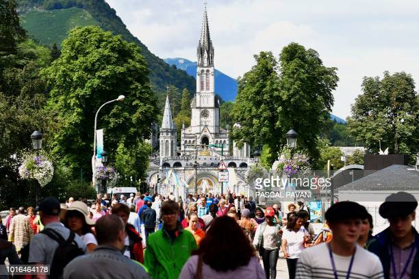 Pilgrims walk near the Sanctuary of Our Lady of Lourdes in the French southwestern pilgrimage city of Lourdes on August 14 a day before the Feast of...