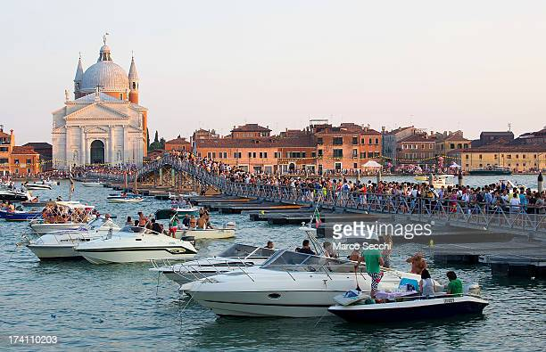 Pilgrims walk on the votive bridge while people gather on boats of all sizes in St Mark's basin for the Redentore Celebrations on July 20 2013 in...