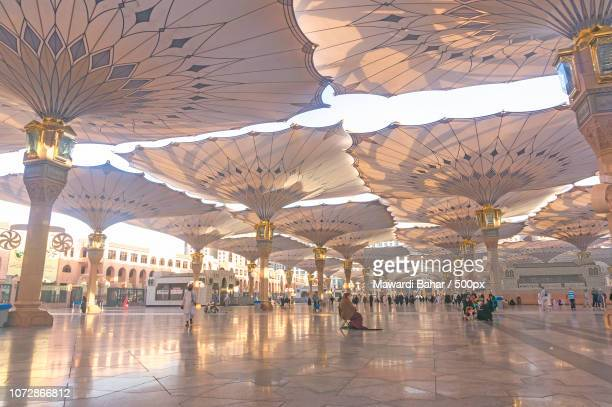 medina - march 06 : pilgrims walk underneath giant umbrellas at nabawi mosque compound on march 06, - al masjid al nabawi stock pictures, royalty-free photos & images