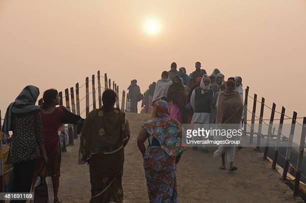 Pilgrims walking on a bridge at Maha Kumbh at sunrise Allahabad Uttar Pradesh India