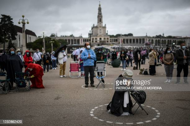 Pilgrims wearing face masks and keeping social distance attend the annual Fatima pilgrimage at the Fatima shrine in central Portugal held under...