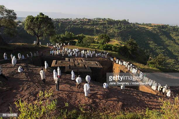 pilgrims wearing traditonal gabi (white shawl) at festival at rock-hewn monolithic church of bet giyorgis (st. george's), roof shaped like a greek cross, lalibela, unesco world heritage site, ethiopia, africa - lalibela stock photos and pictures