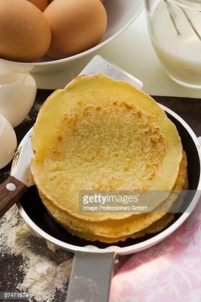 Piling up pancakes in frying pan