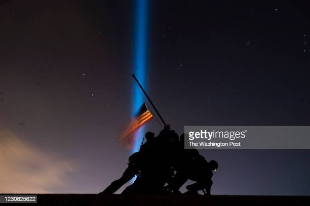 Pillars of light illuminate the sky behind the United States Marine Corps War Memorial, on the eve of the Inauguration of President-elect Joe Biden,...