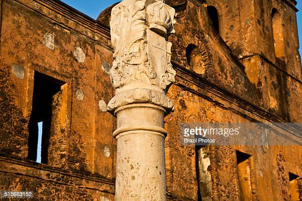 Pillory where criminals and fugitive black slaves were exhibited and punished decorated with the Portuguese empire's weapons In the background the...