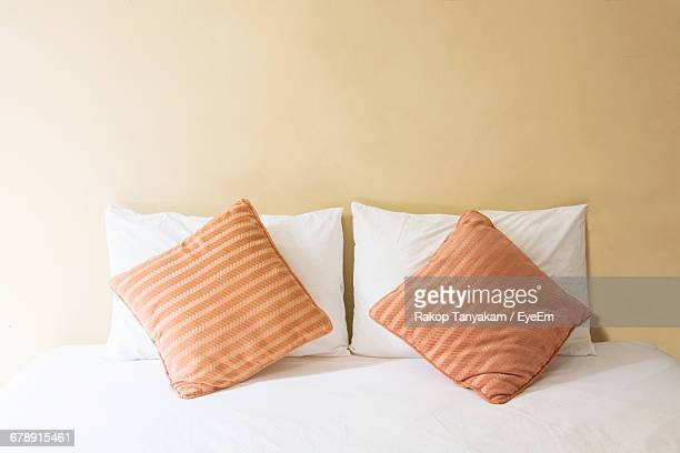 Pillow And Cushions Arranged On Bed At Home