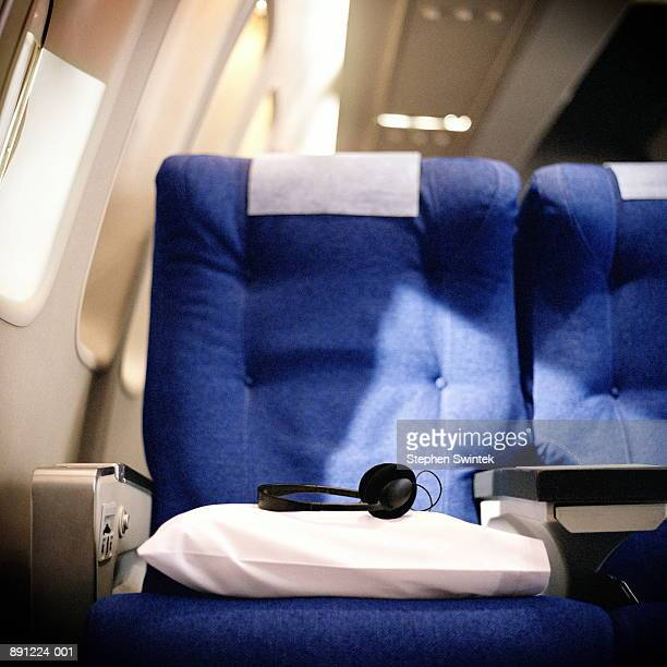 Pillow and headphones on seat in airliner