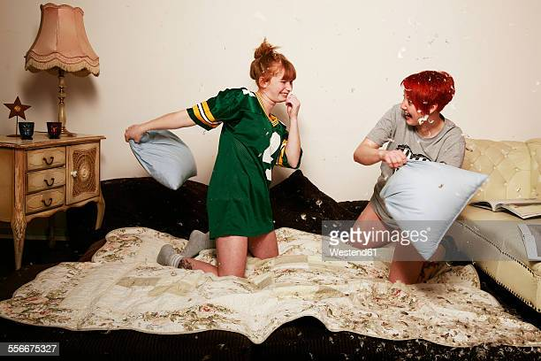 Pillow fight between two female friends at home