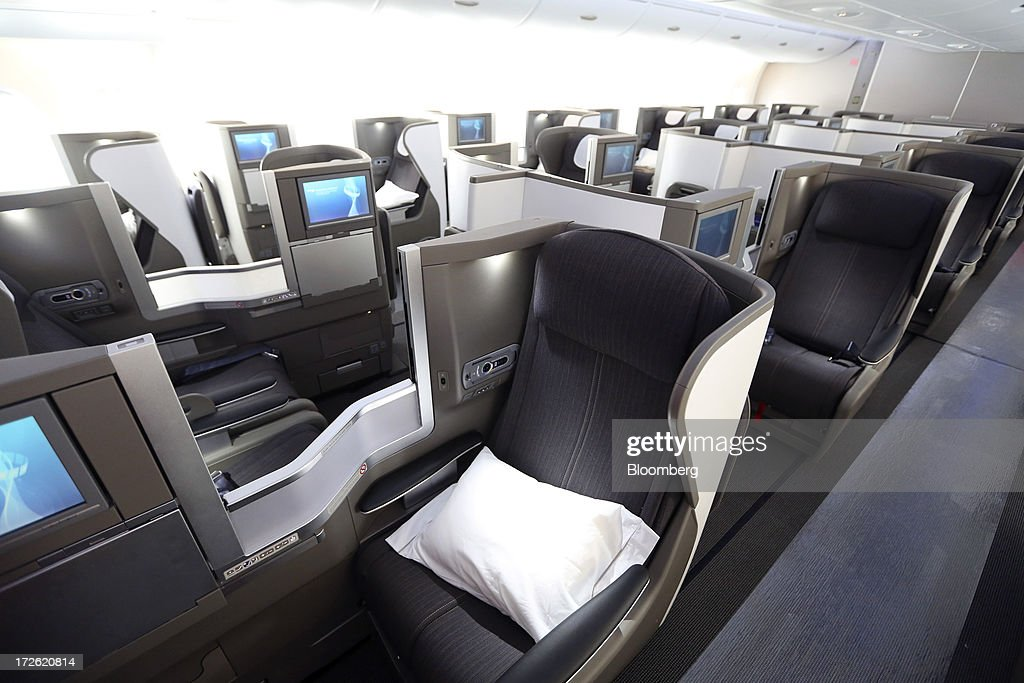 A pillow sits on a booth-style seat in the 'Club World' section of a new Airbus A380 aircraft operated by British Airways (BA) at Heathrow airport in London, U.K., on Thursday, July 4, 2013. British Airways will start regular services with the Airbus SAS A380 superjumbo a week earlier than planned after taking delivery of the first of 12 of the doubledeckers today. Photographer: Chris Ratcliffe/Bloomberg via Getty Images
