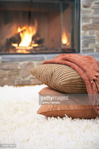 Pillows and blanket near fireplace