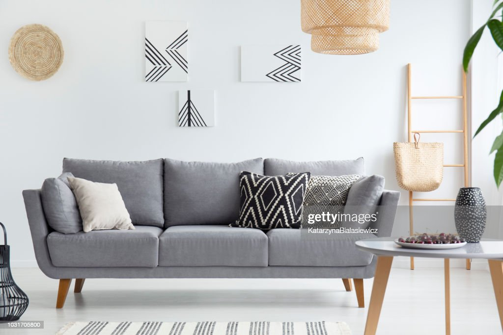Pillows on grey sofa in white living room interior with posters, lamp and wooden table. Real photo : Stock Photo