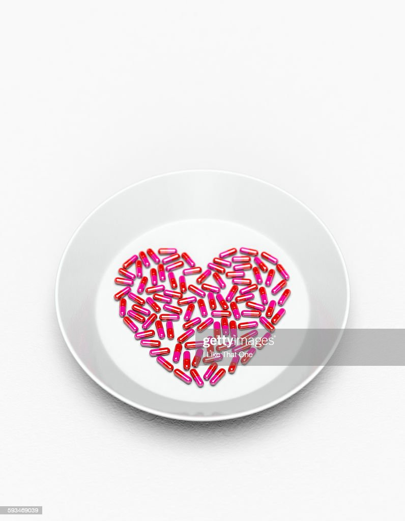 Pills in a heart shape on a white plate : Stock Photo