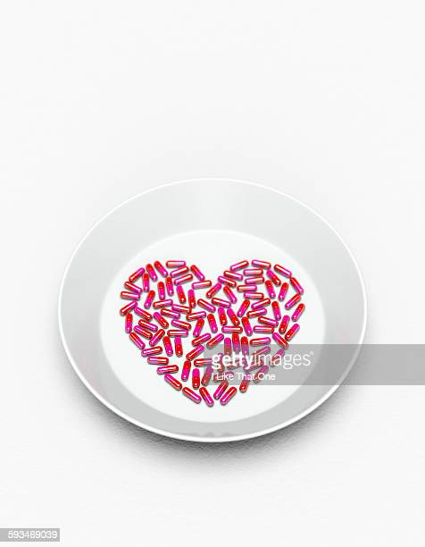 Pills in a heart shape on a white plate