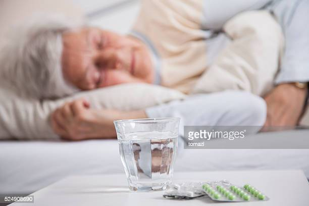 Pills on a night table and senior woman sleeping