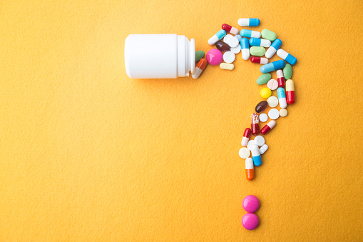 Pills or capsules as a question mark and white plastic bottle. 1026909904