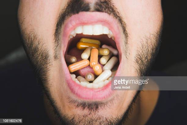 pills, pills in mouth, popping pills, vitamins, supplement pills, pill capsules - hypochondria stock photos and pictures