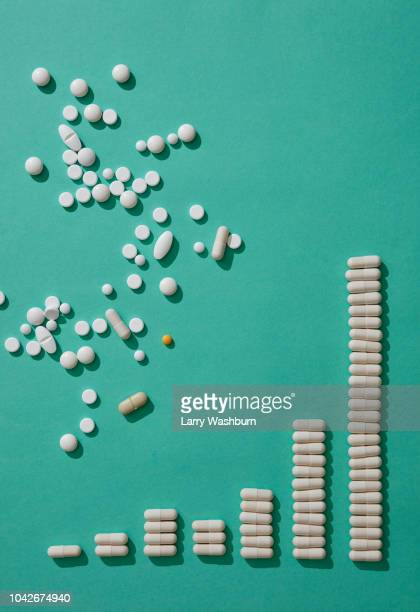 pills scattered above capsules forming ascending bar graph on green backgrounds - dosis stock-fotos und bilder