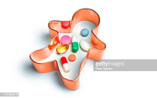 pills sitting inside pastry cutter in the shape of a human body - ibuprofen stock pictures, royalty-free photos & images