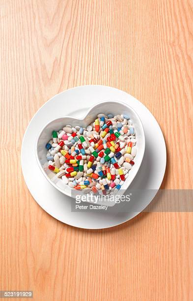 Pills tablets and capsules in heart dish