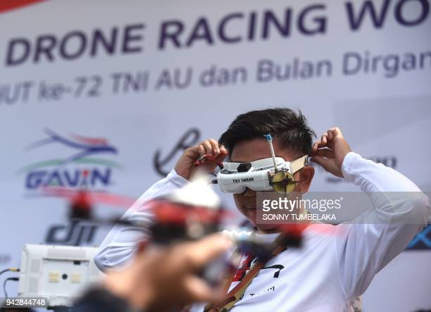 A pilot adjusts his FPV headset goggles during the FAI Drone Racing World Cup event in Denpasar on Indonesia's resort island of Bali on April 7 2018...