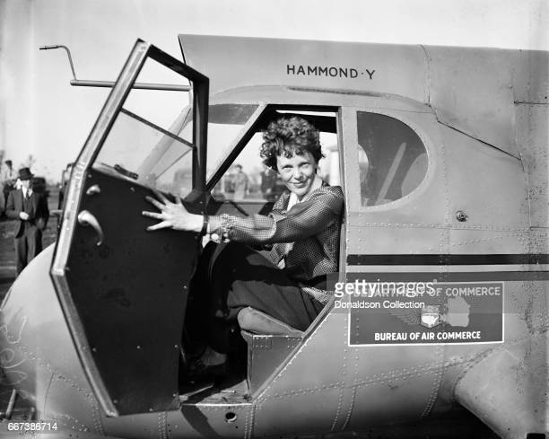 Pilot Amelia Earhart poses for a portrait in and airplane in circa 1936
