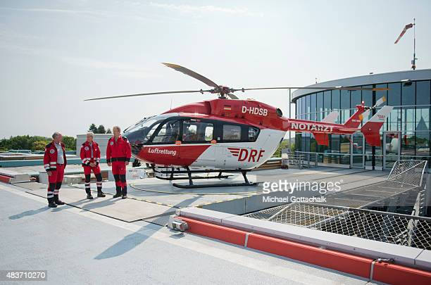 A pilot an emergency doctor and a Paramedic of DRF Deutsche Luftrettung stand in front of a medevac Helicopter or Rettungshubschrauber on August 12...