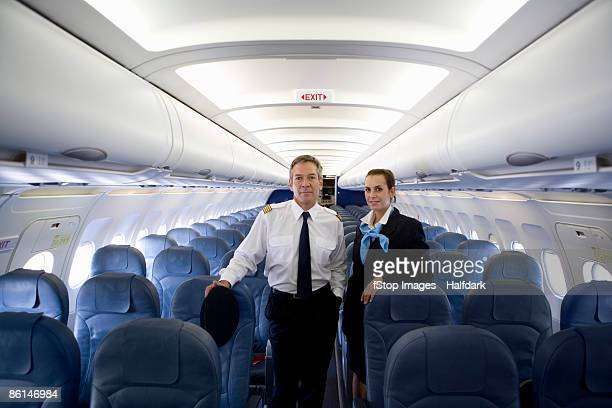 A pilot and a flight attendant standing in the cabin of a plane