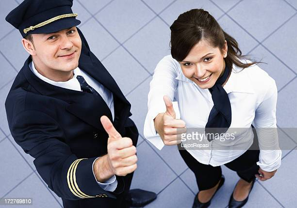 Pilot and a stewardess showing success