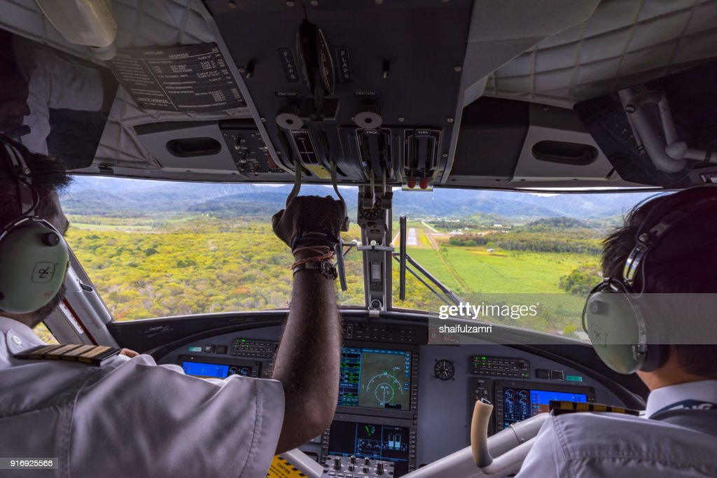 Pilot and co-pilot of MASwings 19-seater Twin Otter aircraft in flight from Miri to Bario which take about 1 hour flight time. Bario is a remote area in Borneo. : Stock Photo