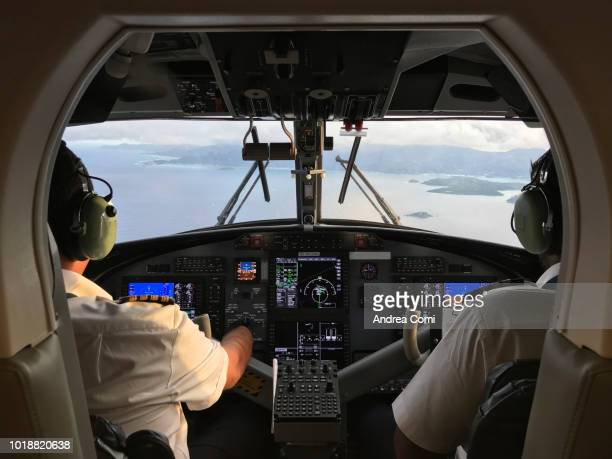pilot and co-pilot piloting aeroplane from airplane cockpit - piloting stock pictures, royalty-free photos & images