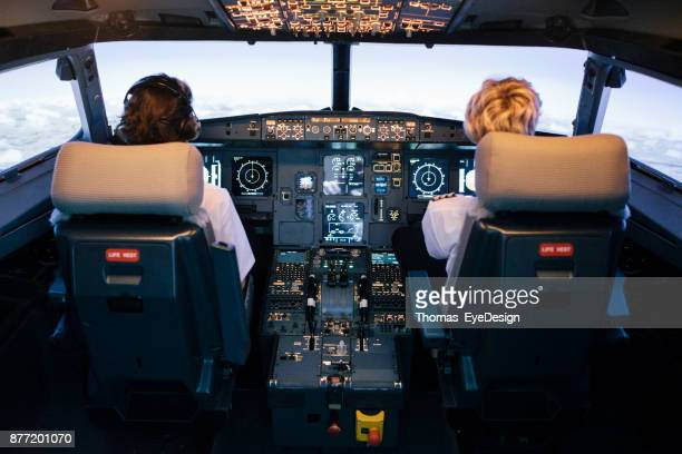 pilot and co-pilot sitting in flight simulator cockpit - cockpit stock pictures, royalty-free photos & images