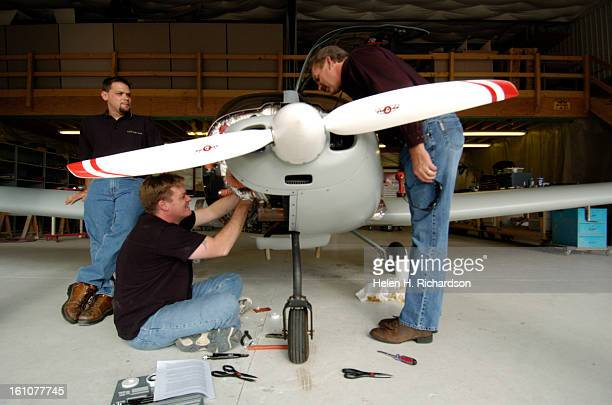 Pilot and designer Bill VonDane, left on ground, works on the engine while Jeff Thomas, right, an investor in the company, checks out the engine of...