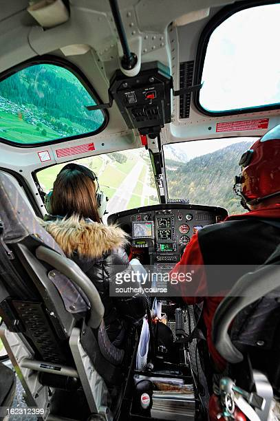 pilot and female passenger in cockpit of a modern helicopter - inside helicopter stock pictures, royalty-free photos & images