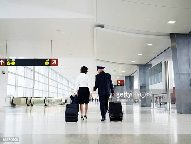 Pilot and flight attendant walking through airport