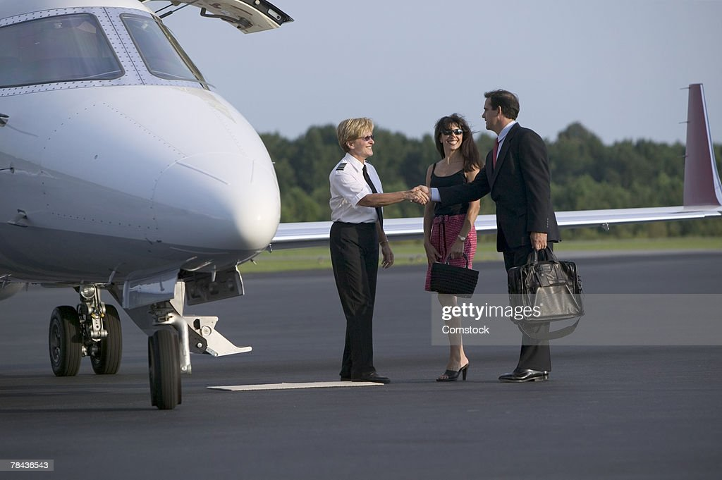 Pilot and passenger shaking hands next to private jet : Stockfoto