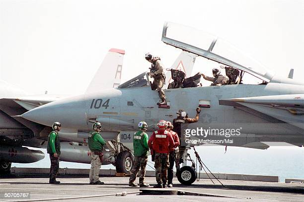 A pilot and Radar Intercept Officer from the Diamondbacks of Fighter Squadron One Zero Two climbing from the cockpit of their F14 Tomcat after...