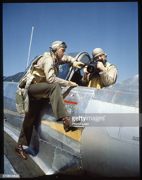Pilot and student aerial photographer with a small camera discuss a mission NAS PENSACOLA Florida February 1944 Plane is an SNJ trainer