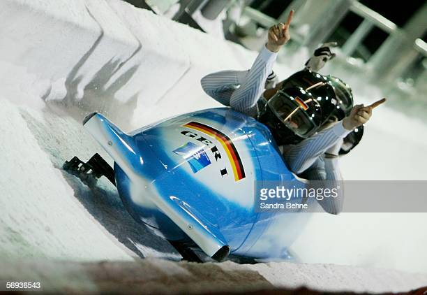Pilot Andre Lange and teammates Rene Hoppe Kevin Kuske and Martin Putze of Germany 1 celebrate their gold medal run in the Four Man Bobsleigh Final...