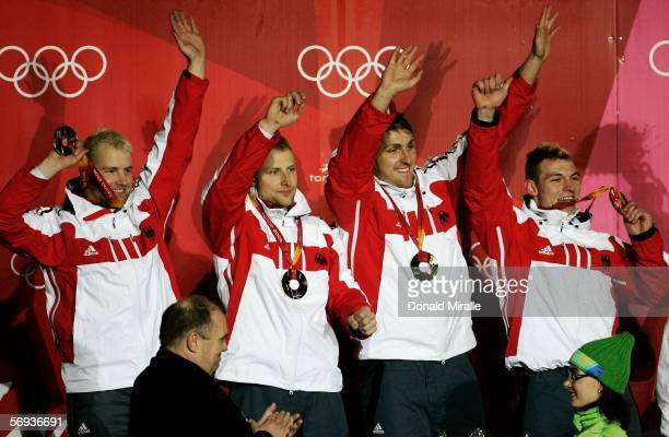 Pilot Andre Lange and teammates Rene Hoppe Kevin Kuske and Martin Putze of Germany 1 celebrate their gold medal in the Four Man Bobsleigh Final on...