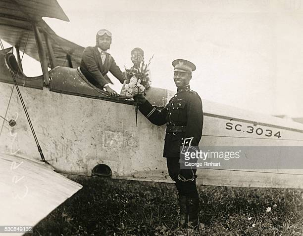 Pilot Bessie Coleman of Chicago the first female African American aviator in the world receiving a bouquet from Captain Edison C McVey in his uniform...
