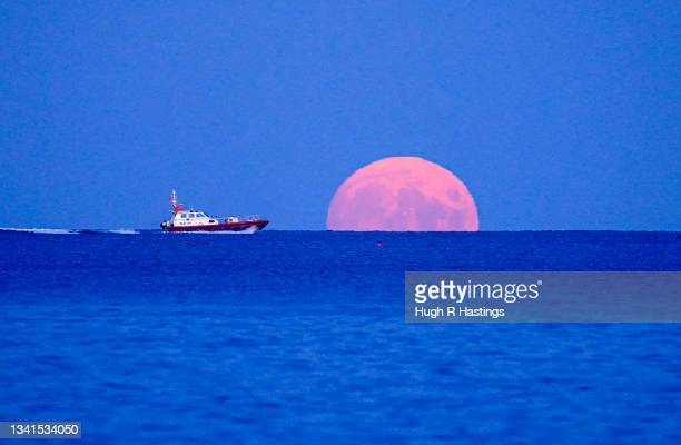 Pilot boat passes the rising Harvest Moon on September 20, 2021 off Swanpool Beach, Falmouth, England.