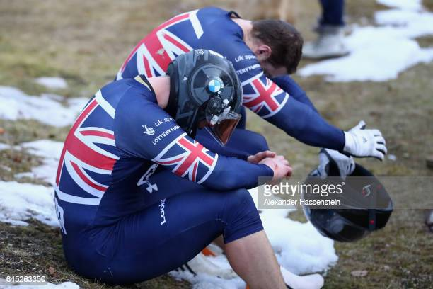 Pilot Bradley Hall of Great Britain reacts with Bruce Tasker after crashing with her team mates Joel Fearon and Gregory Cackett at the second run of...