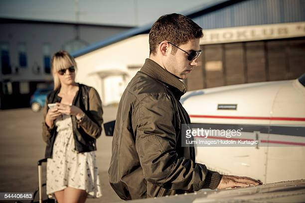 Pilot checking wing of propeller airplane, woman is watching