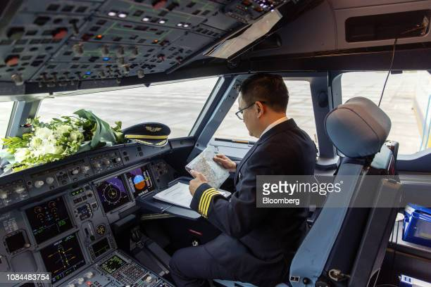 A pilot checks paperwork inside a cockpit on board an Airbus SE A321 Neo aircraft operated by FLC Group JSC's Bamboo Airways at Noi Bai International...